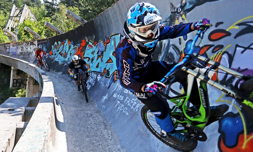 Downhill bikers Kemal Mulic (L-R), Tarik Hadzic and Kamer Kolar train on the disused bobsled track from the 1984 Sarajevo Winter Olympics on Trebevic mountain near Sarajevo, Bosnia and Herzegovina, August 8, 2015. Abandoned and left to crumble into oblivion, most of the 1984 Winter Olympic venues in Bosnia's capital Sarajevo have been reduced to rubble by neglect as much as the 1990s conflict that tore apart the former Yugoslavia. The bobsled and luge track at Mount Trebevic, the Mount Igman ski jumping course and accompanying infrastructure are now decomposing into obscurity. The bobsled and luge track, which was also used for World Cup competitions after the Olympics, became a Bosnian-Serb artillery stronghold during the war and is nowadays a target of frequent vandalism. Picture taken August 8. REUTERS/Dado Ruvic